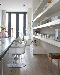 Tussen de twee oude rookkanalen zijn dikke planken gemaakt met daarop kook- en kunstboeken, tijdschriften en een collectie wit porselein.