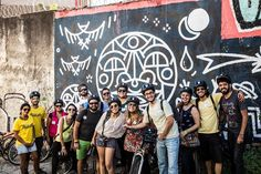 Blogueiros durante o passeio de bike em SP, em frente a um graffiti feito pelo guia Felipe Risada - Foto: Vida Cigana