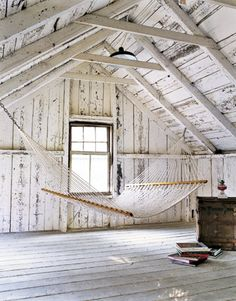 attic hammock with whitewashed walls and a pile of books