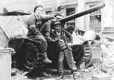 """Early August 1944, Warsaw. Polish barricade on the Napoleon square build around German Jagdpanzer 38(t) """"Hetzer"""" tank destroyer captured by the Home Army.  Photo by Tadeusz Bukowski Source: Wikimedia Commons"""