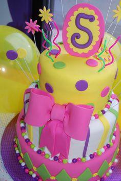 Pink Bow Girl Birthday Cake - Whimsical fondant covered girl birthday cake in yellow, pink, purple and green.