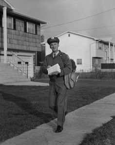 1950s mailman walking outside carrying mail looking at camera