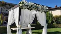 Chuppah in the Wine Country. Top lined with roses, lilies, mums and greens. Small clusters bouquets attached midway down. White sheer drapery adds an elegant flow. Petal Town Flowers
