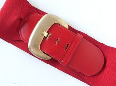 Vintage 1980s belt for vintage lovers! The wide red elastic belt has a stiff leather end, which is called the tongue.