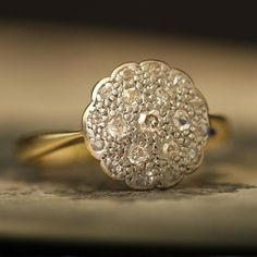 This early Deco/late Edwardian floral cluster is a departure from the traditional daisy motif. The face of this ring is designed to resemble a more densely petaled flower, it glitters with 19 single cut diamonds and wonderful, textured bead work. This ring features narrow tapered shoulders and a half round hoop.    Materials: 18k yellow gold, platinum, 18 x .01ct single cut diamonds, 1 x .03ct single cut diamond (center)  Age: c. 1920  Condition: Excellent  Size: US 5.75, can be resized…