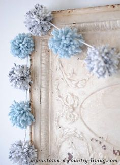 A pom pom garland in two colors of yarn soften a vintage ceiling tin. See how to make this garland for your own home decor.