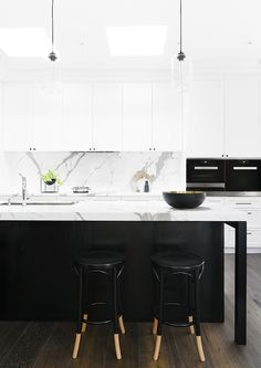 Black and white kitchen: marble benchtop and splashback, white shaker cabinets, black handles, black island cabinetry, black dipped Thonet bar stools, glass pendant lights on black cords, skylights