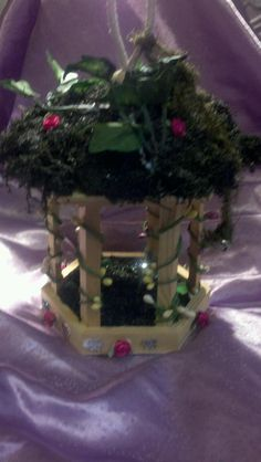 My faerie house created before Faerie Magick Class. Lots of moss, small fabric roses, ivy leaves for the top and twining buds around the pillars.  Glitter and sparkly butterflies around the bottom.