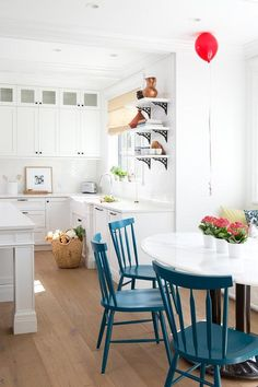 A breakfast nook is filled with a built-in dining bench and window seat facing a black and white oval dining table lined with blue windsor style dining chairs placed atop gray wash wood floors.