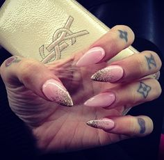 Pale pink stiletto nails with every other glitter tips...