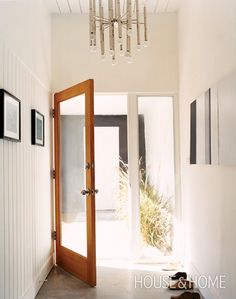 Actress Kathleen Robertson's Entryway  A wood-and-glass door and Jonathan Adler light fixture nod to this home's mid-century design.   The entrance to this Palm Springs, post-and-beam house strikes a beachy, minimalist note. Vintage shoe forms and paintings add whimsy while the windows look onto waving grasses.  See more of Kathleen Robertson's home in our November 2008 issue.