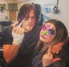 Norman Reedus painting a fans face.