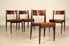 Gruppo di quattro sedie; legno di palissandro, imbottitura in espanso, rivestimento in similpelle. Discrete condizioni, presentano alcuni segni di usura. Altezza seduta:46.