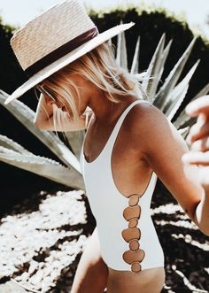 white one piece bathing suit with o ring lace up side slit. spring summer resort wear outfit inspiration for women. beach with straw hat and sunglasses