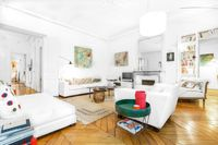 The Avenue Trudaine Residence located in South Pigalle, Paris   Luxurious family sitting room with shuttered windows, modern art, TV, fireplace, easy chairs and artistic details. #kidandcoe #propertyoftheday