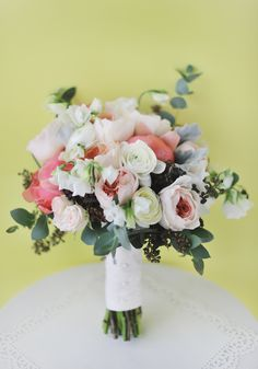 Bouquet by Garden Party Flowers in Vancouver. From the florist: This bouquet is ideal for a romantic, soft, vintage spring wedding. It has a natural and organic flow and was inspired by coral peonies. Flowers: Juliet garden roses, white sweet peas, coral peonies, white ranunculus, dusty miller, seeded eucalyptus, guni eucalyptus. Photography by Hong Photography .