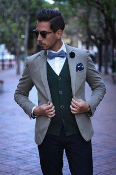 Ray Ban club master sunglasses, Khaki cotton blazer with button able cuffs, White Shirt, Blue chambray bow tie, Green cardigan, White polka dots on denim pocket square, blue skinny chinos