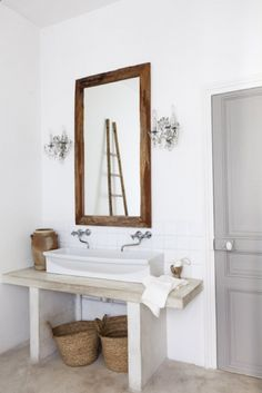 Simple and clean bathroom with white walls, wooden accents (mirror and ladder), raised sink, simple vanity, and chandeliers on each side of the mirror