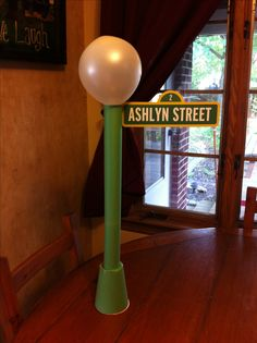 DIY Sesame Street sign. Made using 2 paper towel rolls, a red solo cup, white balloon, and green construction paper! Tape all the pieces together, cover with construction paper and print your own personalized sign :)