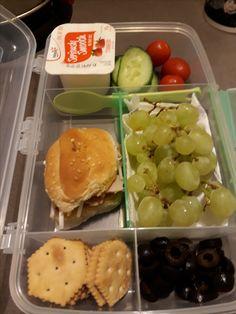 Ham and cheese slider, yogurt, fruits, veggies, olives and crackers.