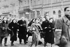 Jews are marched through the streets of the Warsaw ghetto on the way to the railway for 'deportation'.