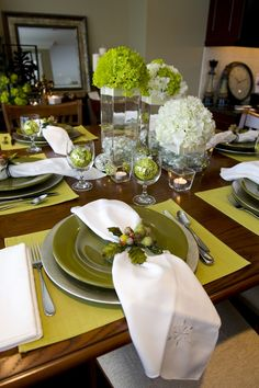 A festive holiday place setting on a light green placemat. The white napkin has an embroidered snowflake on the edge. The napkin ring is made to look like a bunch of holly.