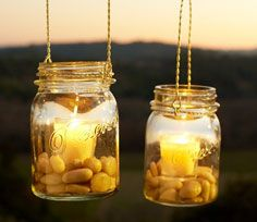 Mason Jars, pretty stones, a simple chain and a bright candle! Do-it-yourself lighting for your backyard patio. I love this!