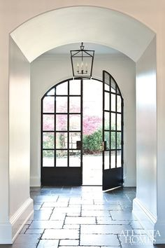 striking and classic black iron front doors with simple lantern and stone floors