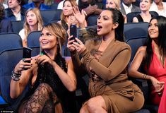 Chrissy Teigen and Kim Kardashian used their phones to snap photos as their husbands picked up their award