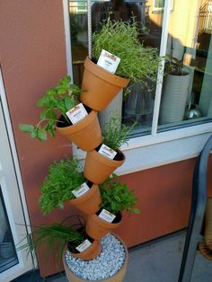 Brilliant idea executed by a friend: big pot with a steel rod held in place by pebbles (making a permanent solution with concrete might be more stable). She threaded terracotta pots on the rod and planted her herbs in them.