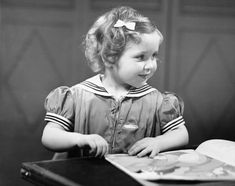 An poster sized print, approx mm) (other products available) - Young girl at table reading book, (B&W) - Image supplied by Fine Art Storehouse - poster sized print mm) made in the UK