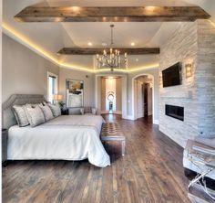 Master Bedroom- floor to ceiling stone fireplace, hardwood floor, pendant chandelier, wood beams