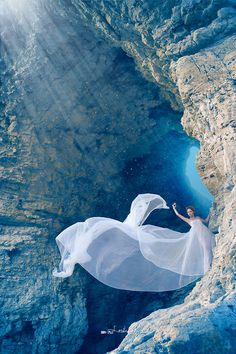 woman in flowing gown on edge of cave