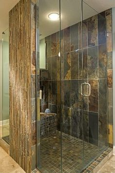A truly custom designed shower using slate tiles and frameless glass shower door surround
