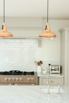 deVOL Kitchens Save Email Copper + nickel When you're craving a hint of copper to add flair to a classic kitchen, try adding bright copper pendant lights. Team them with warm-toned nickel for taps and cabinet handles – a polished finish is particularly luxe against this sludgy greige cabinetry.