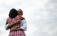 First Lady Michelle Obama and President Obama hug after delivering remarks during a campaign event at the Alliant Energy Amphitheater in Dubuque, Iowa, on Aug. 15 during his three-day campaign bus tour across the state. (Jim Watson/AFP/Getty Images)