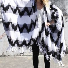 """SALE K'isbal Poncho    Material Content:100% Cotton    One Size:70"""" Sleeve to Sleeve & 36"""" Shoulder to Fringes    Handmade in Guatemala    Colors:Black and White    Our ponchos are handmade by skilled artisans in Guatemala. Each poncho is made with care and dedicated skill and is one of a kind! 