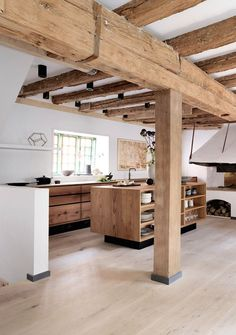 A beautiful kitchen design by Gardehvalsoe, using Dinesen HeartOak, for both the kitchen cabinets and the flooring, the kitchen sink is burnished brass. Love the exposed beams and old cooking range in