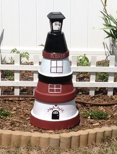 Lighthouse made from various size garden pots and one solar yard light. During the day the solar panel charges and at night it lights up my garden! by gwendolyn Clay Pot Projects, Clay Pot Crafts, Flower Pot Crafts, Flower Pots, Flowers, Solar Yard Lights, Clay Pot Lighthouse, Deco Kids, Painted Clay Pots