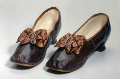 1860s ladies' bronzed leather heeled shoes with silk bows and mock buckles. Schweizerisches Nationalmuseum. [jrb]