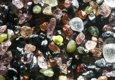 The glacially deposited sands around Lake Winnibigoshish, Minnesota, contain abundant sediments from the igneous and metamorphic minerals of the Lake Superior basin. A sample includes pink garnets, green epidote, iron-rich red agates, black magnetite, and hematite.