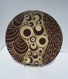 This great-looking round platter was built by hand from a slab of white stoneware clay, then covered with a red-brown underglaze and carved before it was fired. This technique is called sgraffito, and it reveals the white clay body underneath the underglaze. It is a very time consuming process- but it produces great-looking results! I enjoy the carving of my pieces, as I find it to be a bit of a relaxing process. I use no template - just freehand it as I go along. No two of my pieces ever…