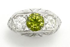 An alluring, exotic Russian demantoid garnet and diamond three stone Art Deco engagement ring. Rare, green garnets are seldom seen, especially in this size. At 1.50 carats and with a lush, vivid olive green, enticingly set between a pair of chunky, sparkling old European diamonds of 3/4 carats each. #antique #demantoid #garnet #3stonering #3stonerings #threestonering #threestonerings #ido #love #artdeco #artdecoring #engagementring #engagementrings #antiquering #antiquerings #vintage… Estate Engagement Ring, Antique Engagement Rings, Old Rings, Antique Rings, Hand Jewelry, Art Deco Ring, Three Stone Rings, Stone Art, Garnet