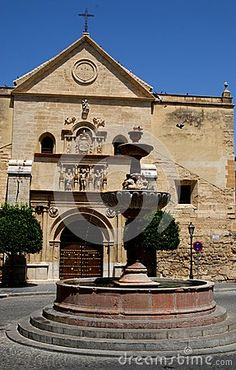 Photo made in Antequera in Spain. The picture shows, in the foreground, a fountain placed in the middle of a square in front of the facade of a simple but ancient small church.