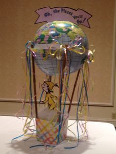 Oh The Places You'll Go centerpiece. Globe beach ball, basket from dollar store, bamboo sticks, Home Depot, clip art banner + yellow guy