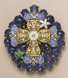 A gem-set, enamel and gold brooch the front centering an antique Bysantine cross pendant with blue, black, and white enamel and accented with two star-shaped clusters, one of diamonds the other of emeralds, the reverse set throughout with a sapphire, ruby, peridot, blue zircons and rose-cut diamonds (some stones deficient), all within a surround of cabochon sapphires; length 2¾in.