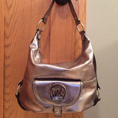 Michael Kors Pewter shoulder bag BOGO 50% off handbags of equal or lesser value! This bag is gorgeous. Shiny leather in pewter (dark silvery gray). It's in perfect condition with the silk white dust bag enclosed. Flap pocket on front. Inner zipper compartment and 3 pockets. Very good construction and comfortable to hang over the shoulder or hang from the arm. I wish I could post more photos! It goes with anything and adds that extra glam with the subtle shimmer. It's the perfect accessory…