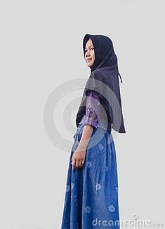A Little girl wear a black hijab and smiling. staring with her smile and isolated in the white background.