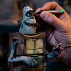 Go Behind the (Crazy-Complex) Scenes of The Boxtrolls | Boxtroll Fish in the hands of an animator armed with an Exacto knife. All of the puppet's movements are manipulated by hand, even their tiny eyeballs. Each Boxtroll is named for the label on his box, and Fish's sardine can gives him a nice bit of sartorial flair.  Jose Mandojana  | WIRED.com