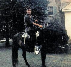 Elvis Presley on one of his horses at Graceland
